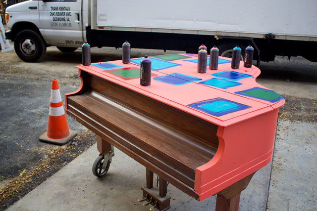A grand piano being spray painted