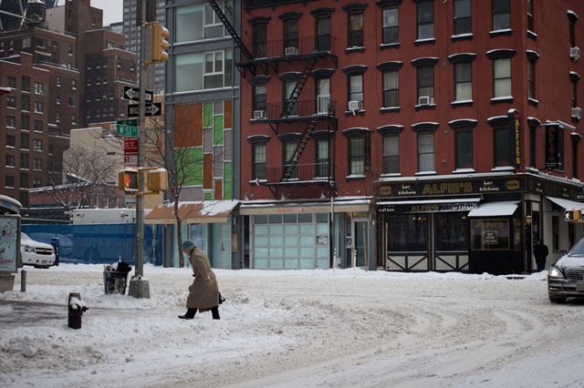 A man walking through snow on 9th Ave