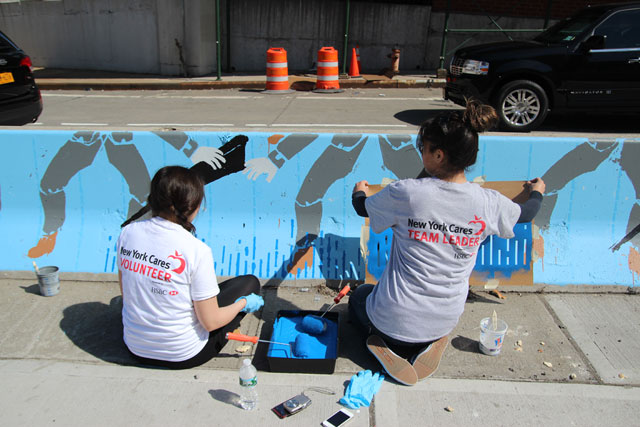 Volunteers painting the art piece at the pedestrian plaza